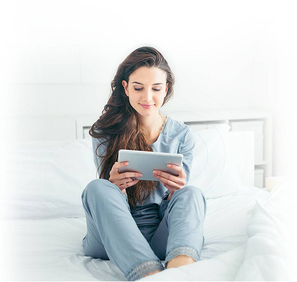 user with tablet on the bed